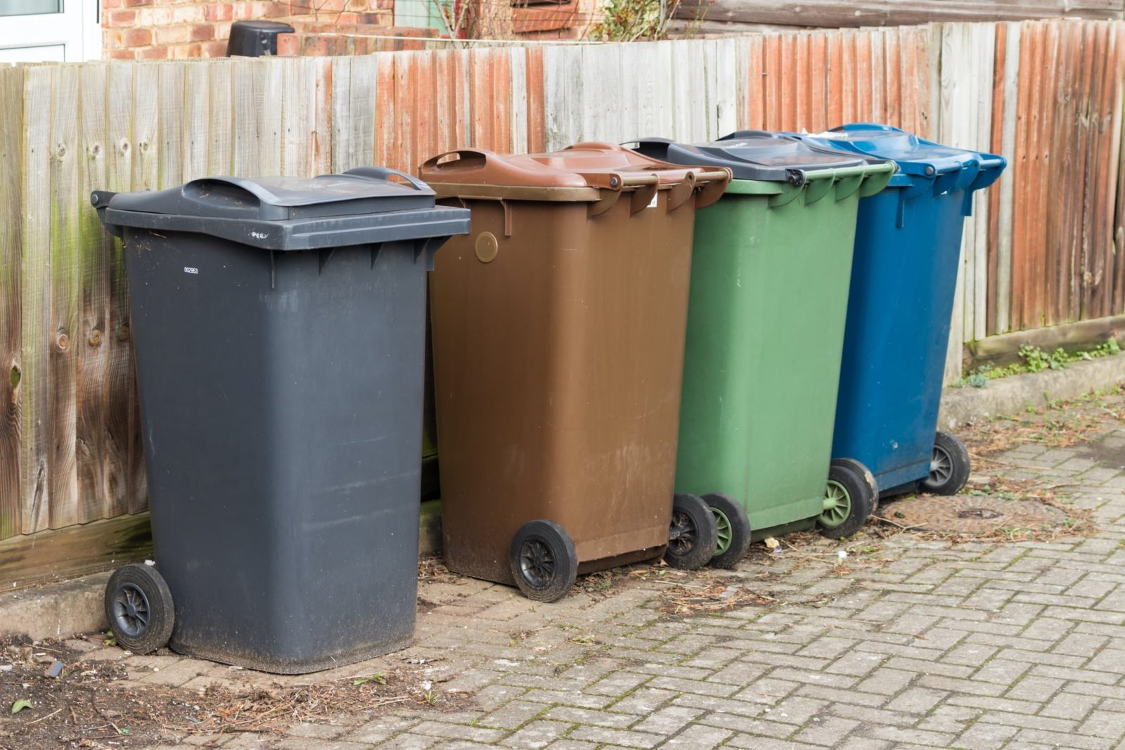 four wheelie bins of different colours