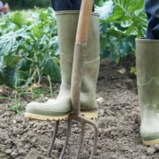 man in wellies using garden fork
