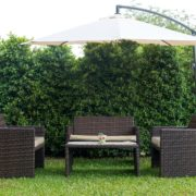 rattan furniture on garden lawn covered by cantilever parasol