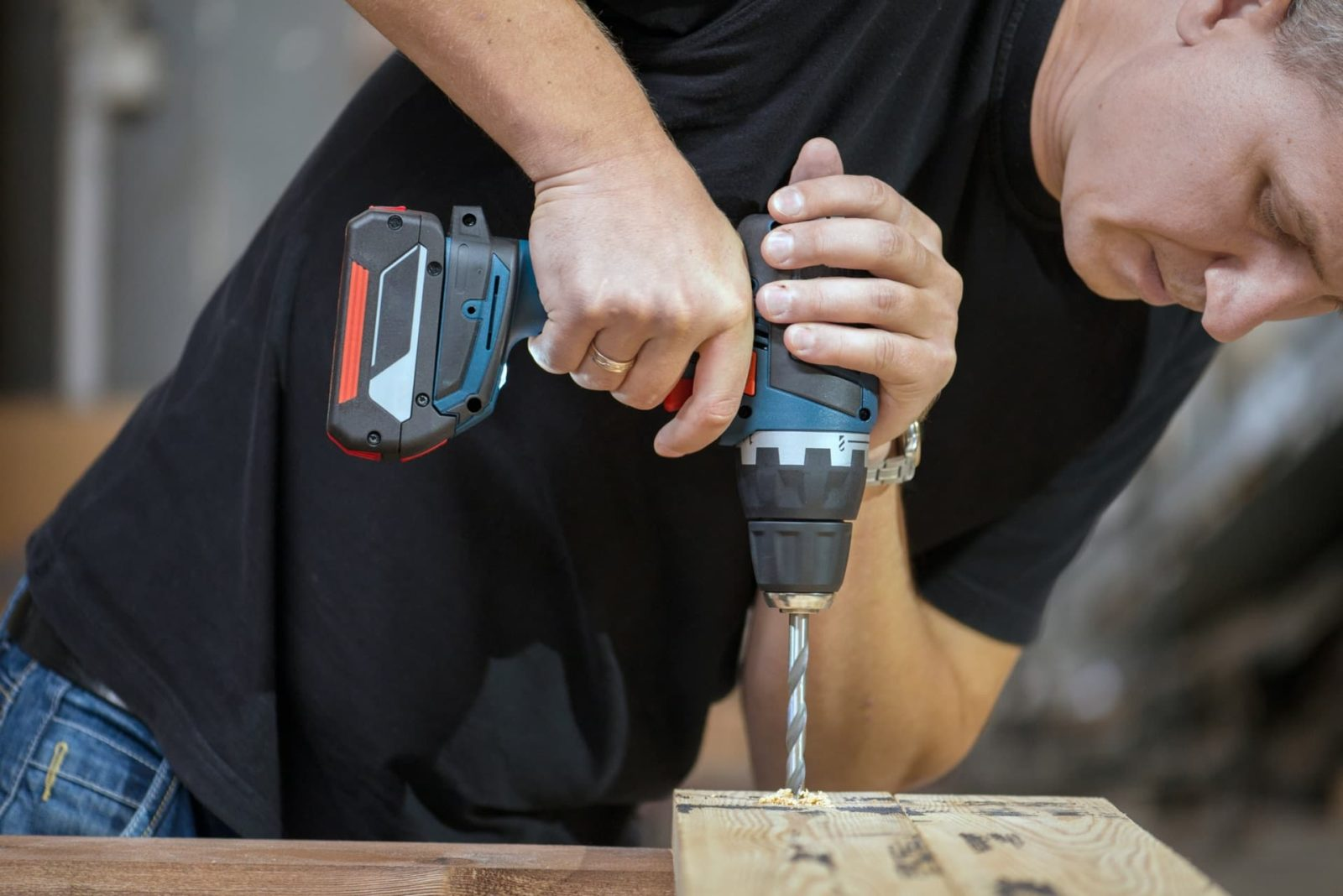 man drilling into timber with force