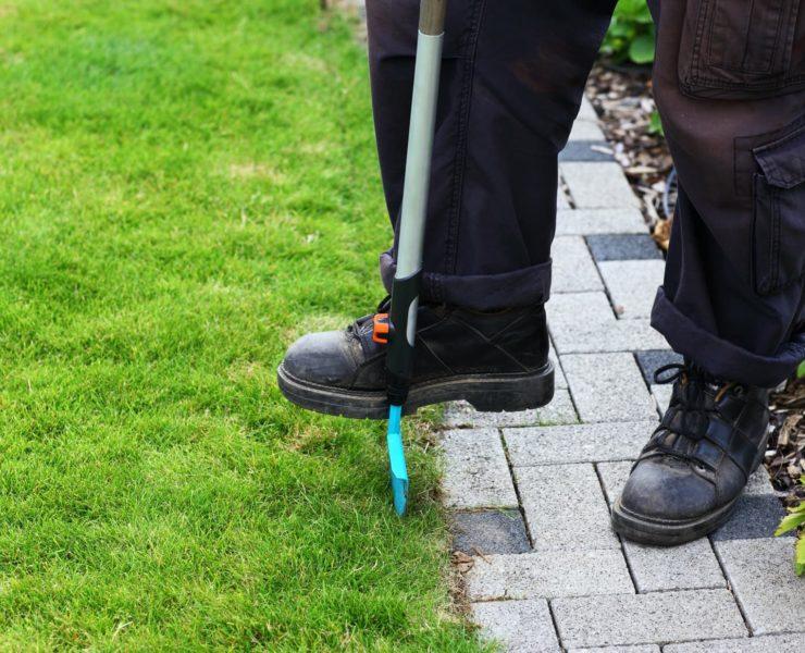 man cutting edge of garden lawn