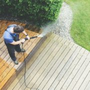 man blasting decking surface with pressure washer