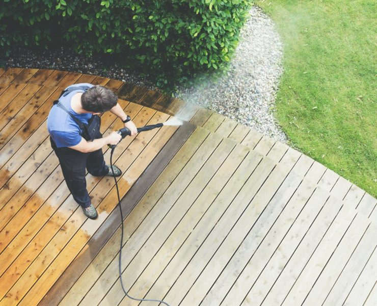 man blasting decking surface with pressure washer