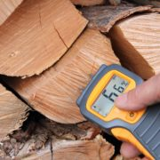 man measuring moisture content of logs