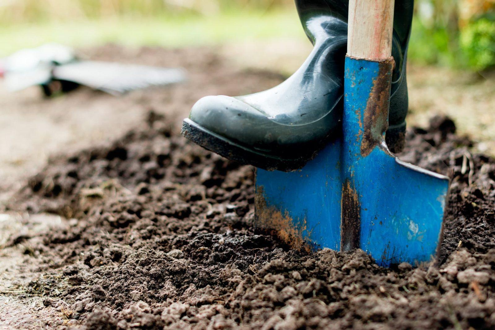 boots push shovel into soil