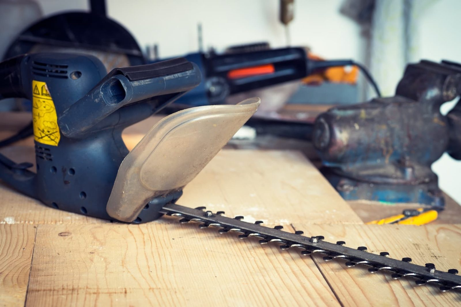 hedge trimmers being sharpened on a workshop table