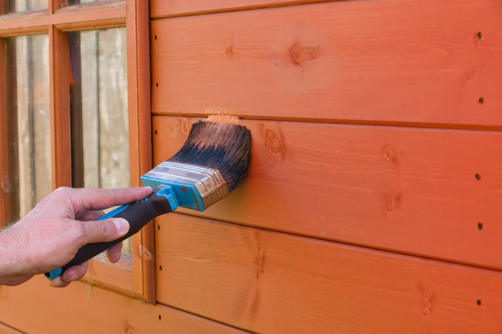 A wooden shed being painted in a red colour