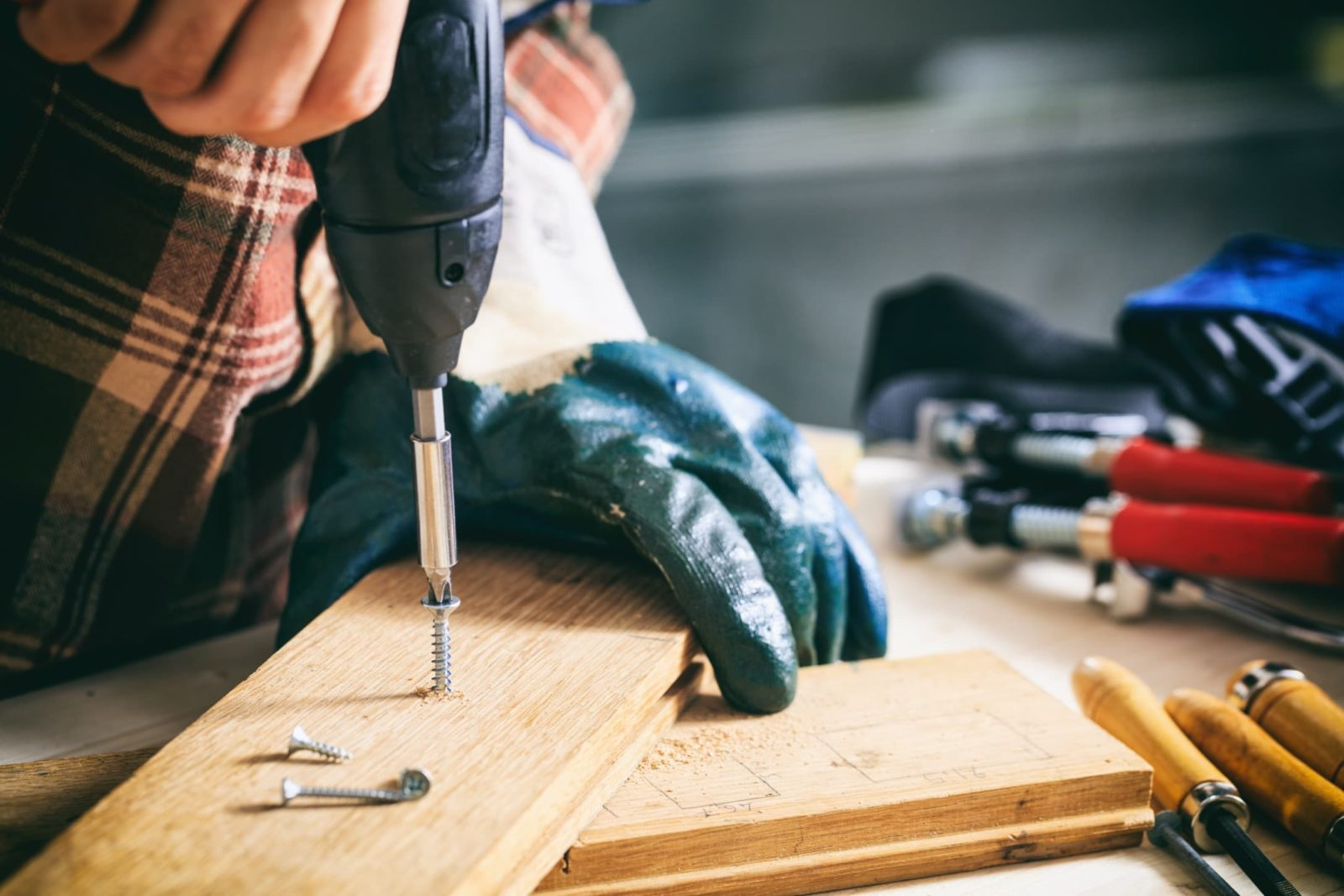man with gloves drilling into wooden board