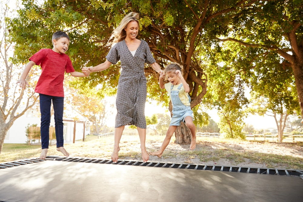 a mother and two children using a sunken trampoline