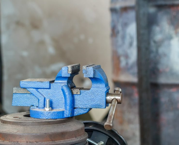 a blue bench vice in a workshop