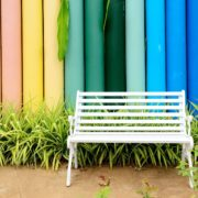 white bench with plants and multicoloured fence in background