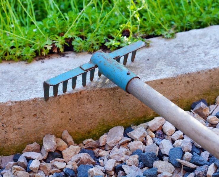 rake lying in garden next to gravel