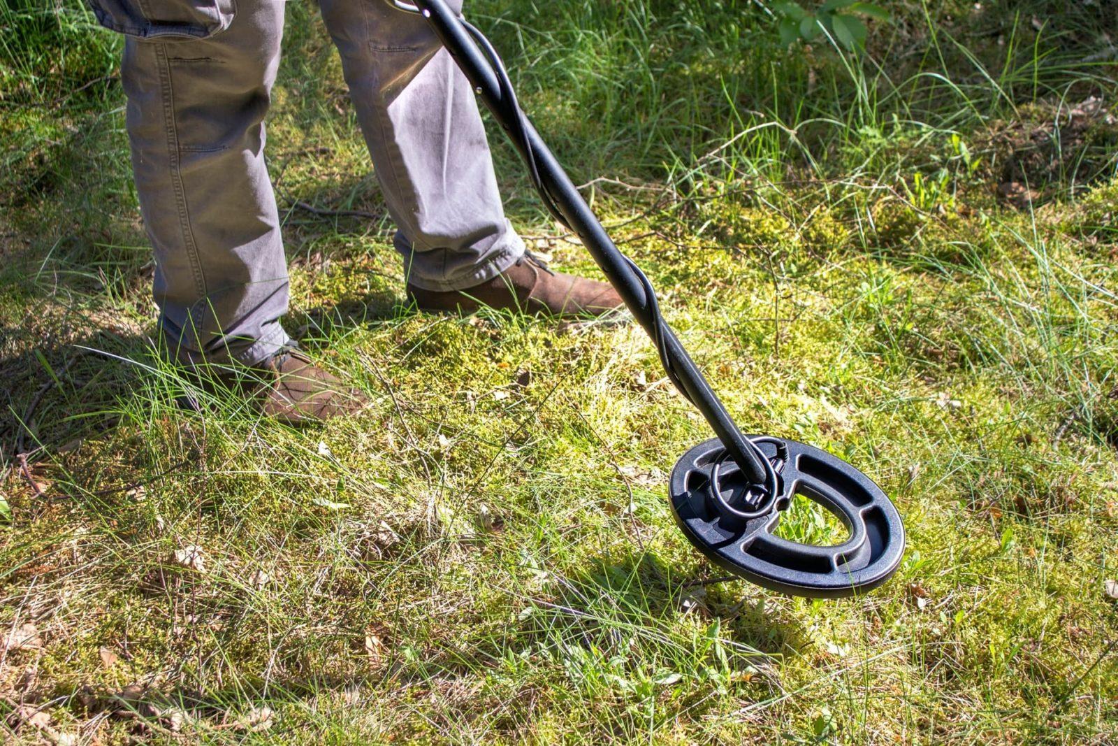 man using metal detector over grass field