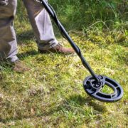 man using metal detector over grass field