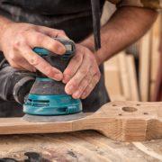 carpenter using random orbital sander in workshop