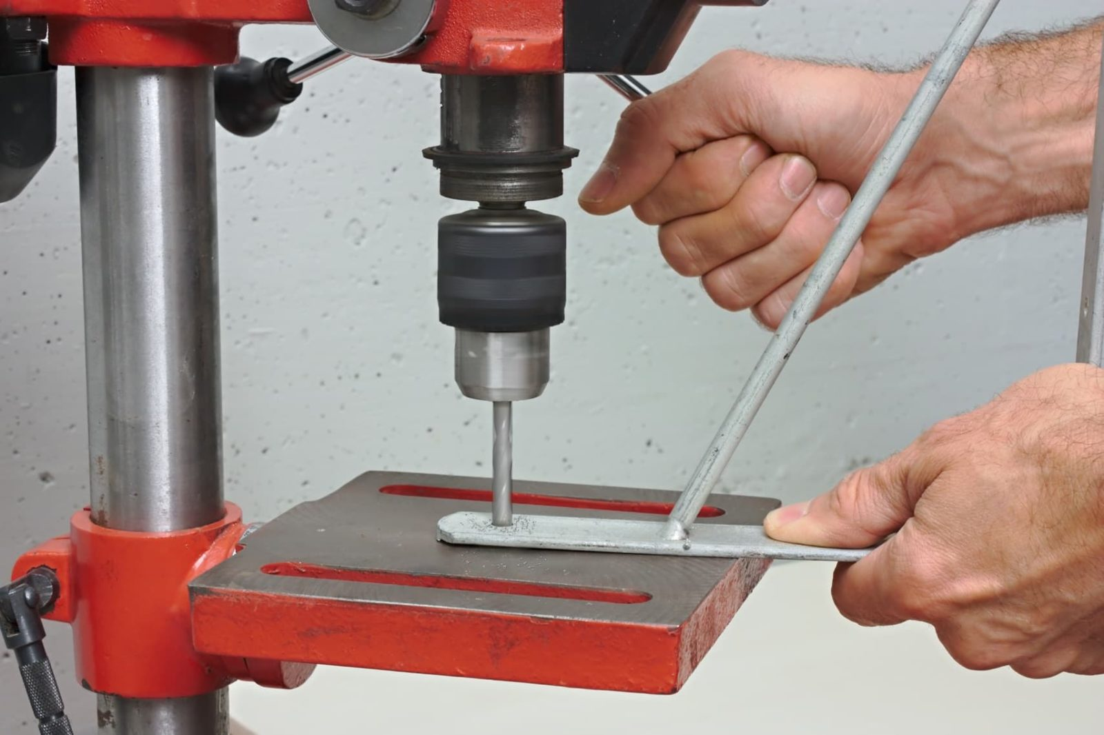 a worker drilling a hole in a metal bracket using a pillar drill