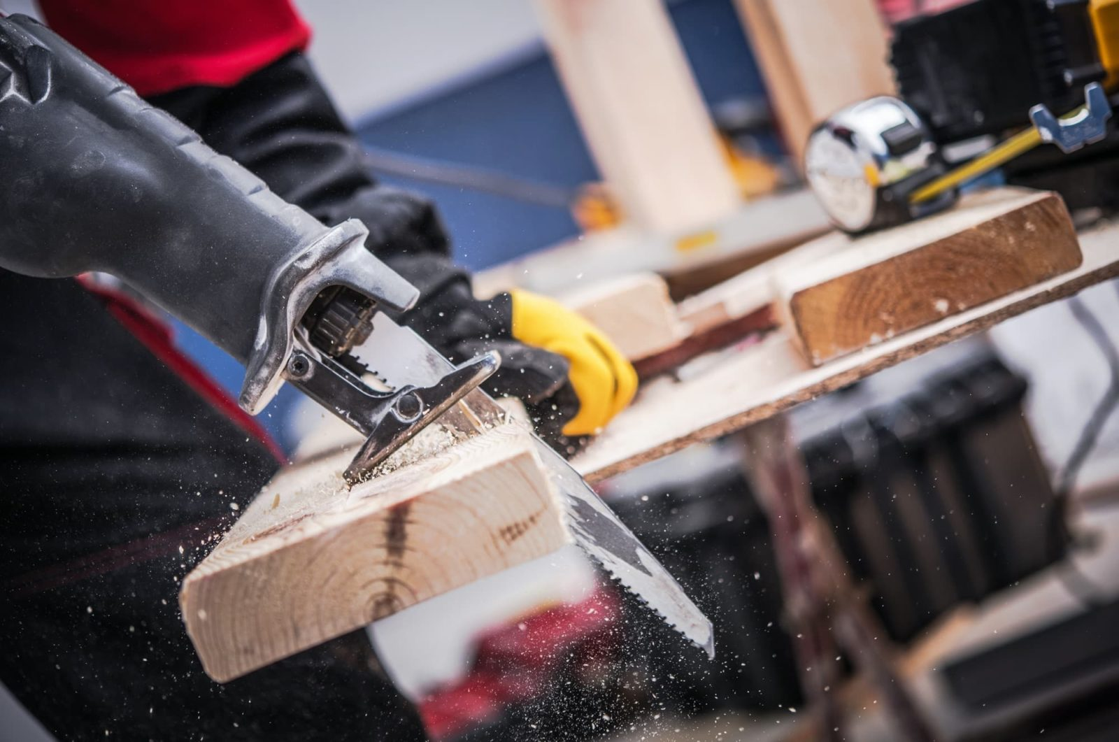 workman using a reciprocating saw to cut through timber on a worktable