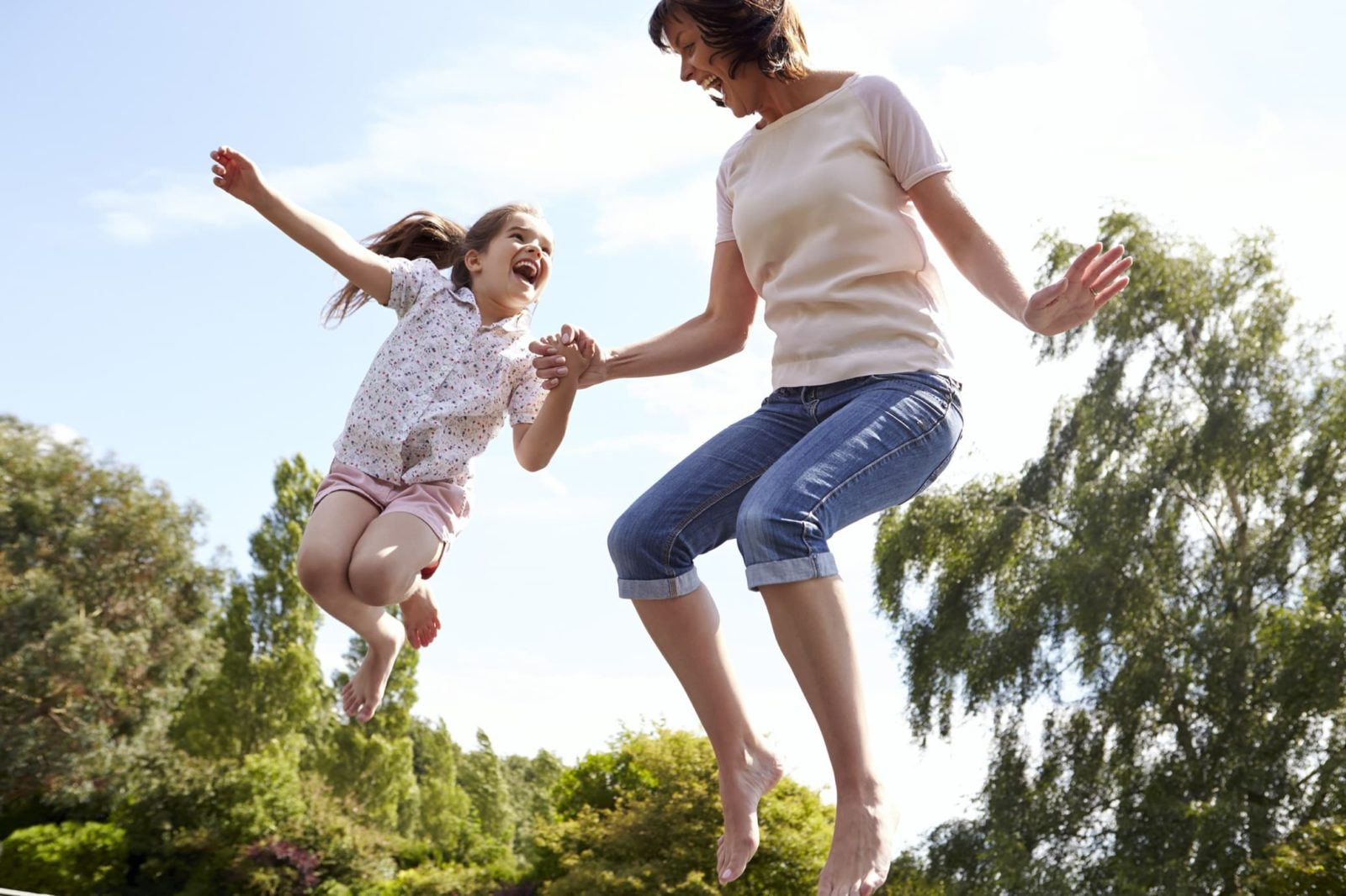 mother and daughter bouncing on a trampoline