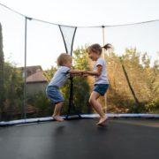 siblings having fun jumping on a trampoline