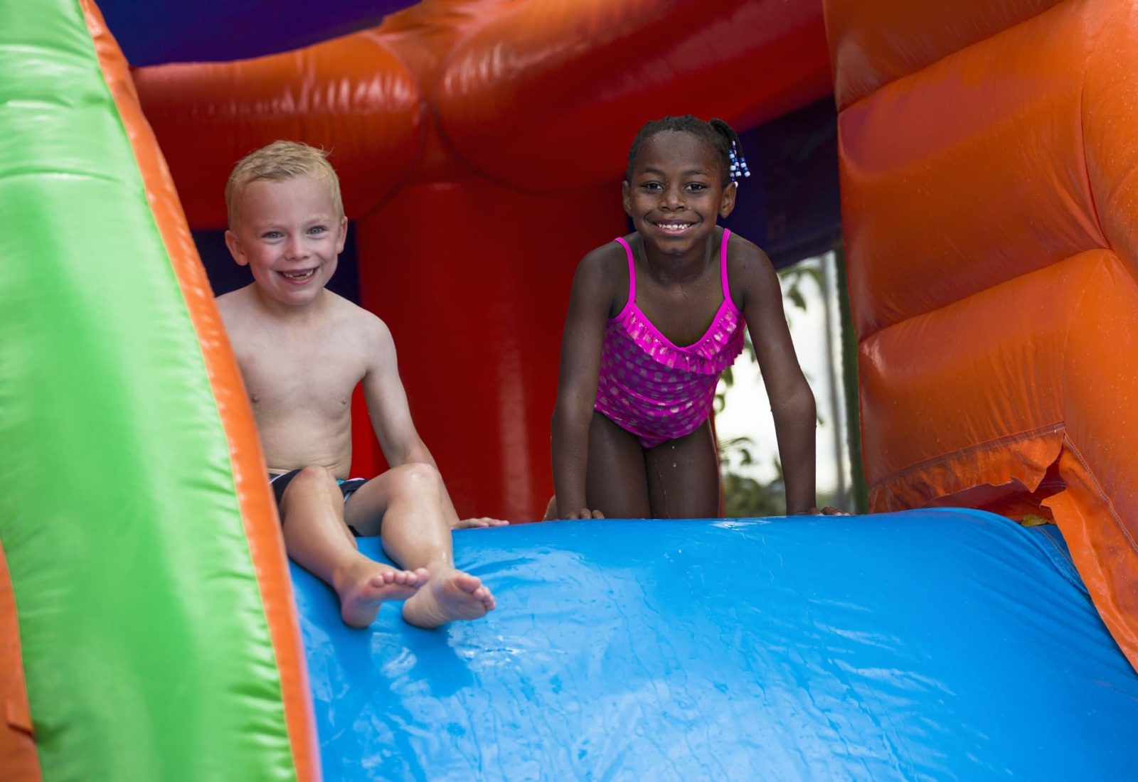 two children sitting at the top of a water slide