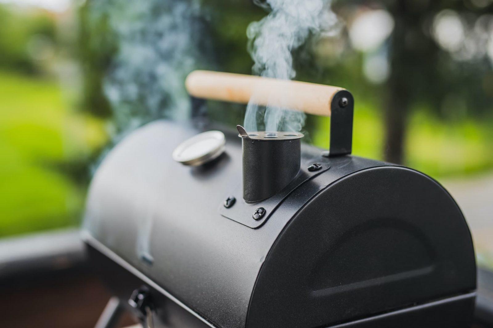 smoke pouring from bbq smoker in garden