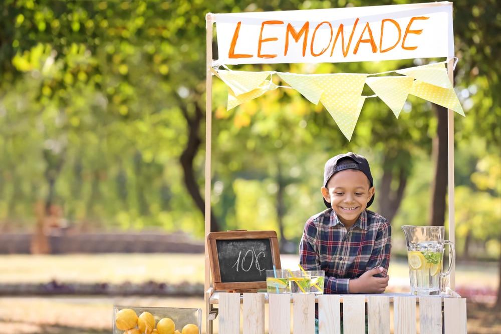 kid selling lemonade on stall in garden