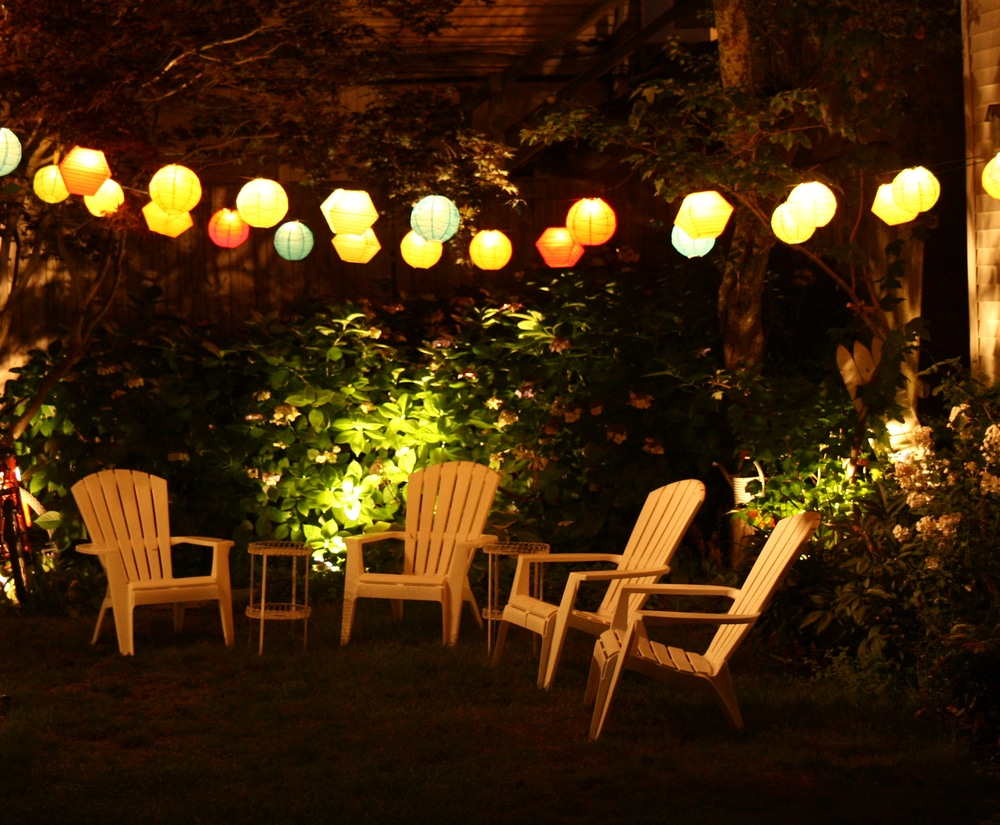 plastic garden chairs in a garden lit up at night