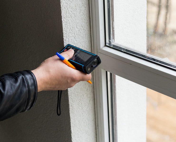laser measure being used on window