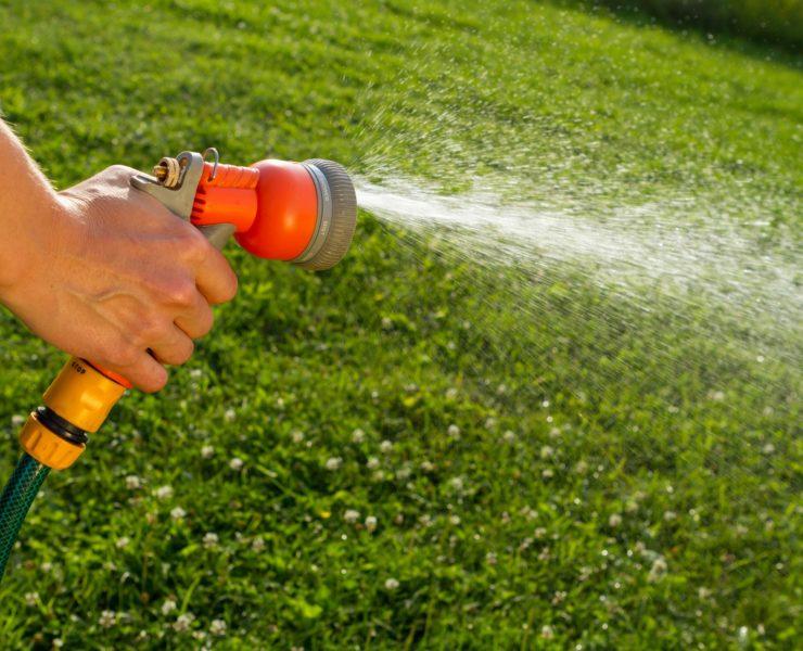 man holding garden hose spray gun