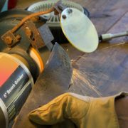man in yellow gloves using angle grinder