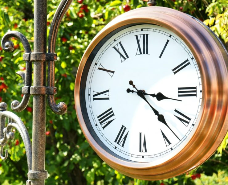 gold garden clock with foliage in background