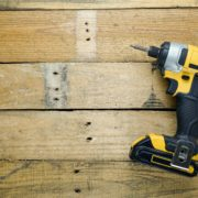 yellow impact driver sat on timber workbench