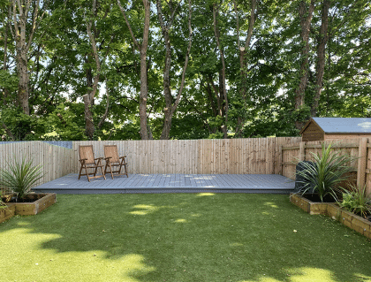 stunning renovated garden with clean cut grass and raised decking at the end of the plot