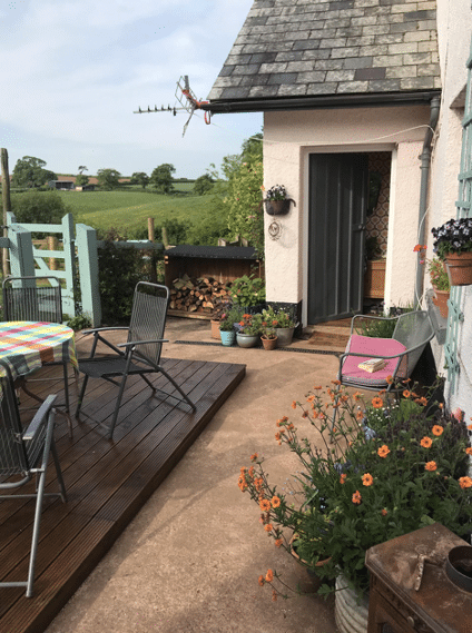 fully renovated outdoors with raised decking and garden furniture
