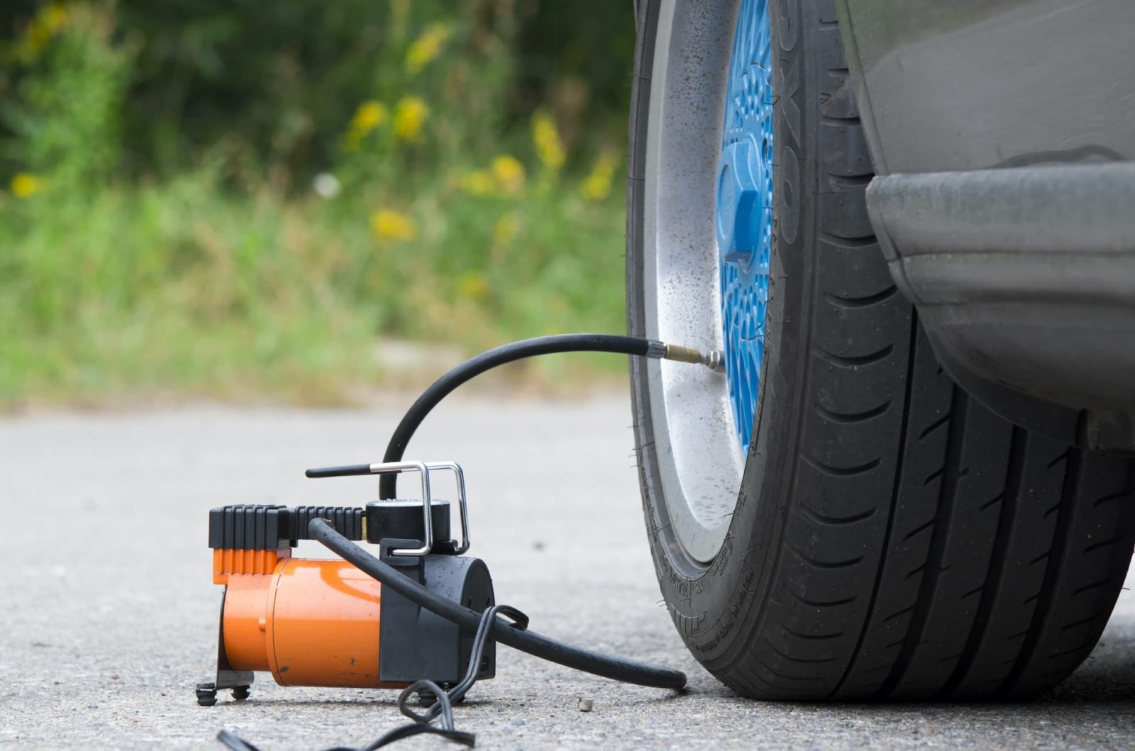 air compressor being used to pump up a car tyre