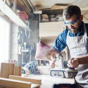 man using belt sander in home garage