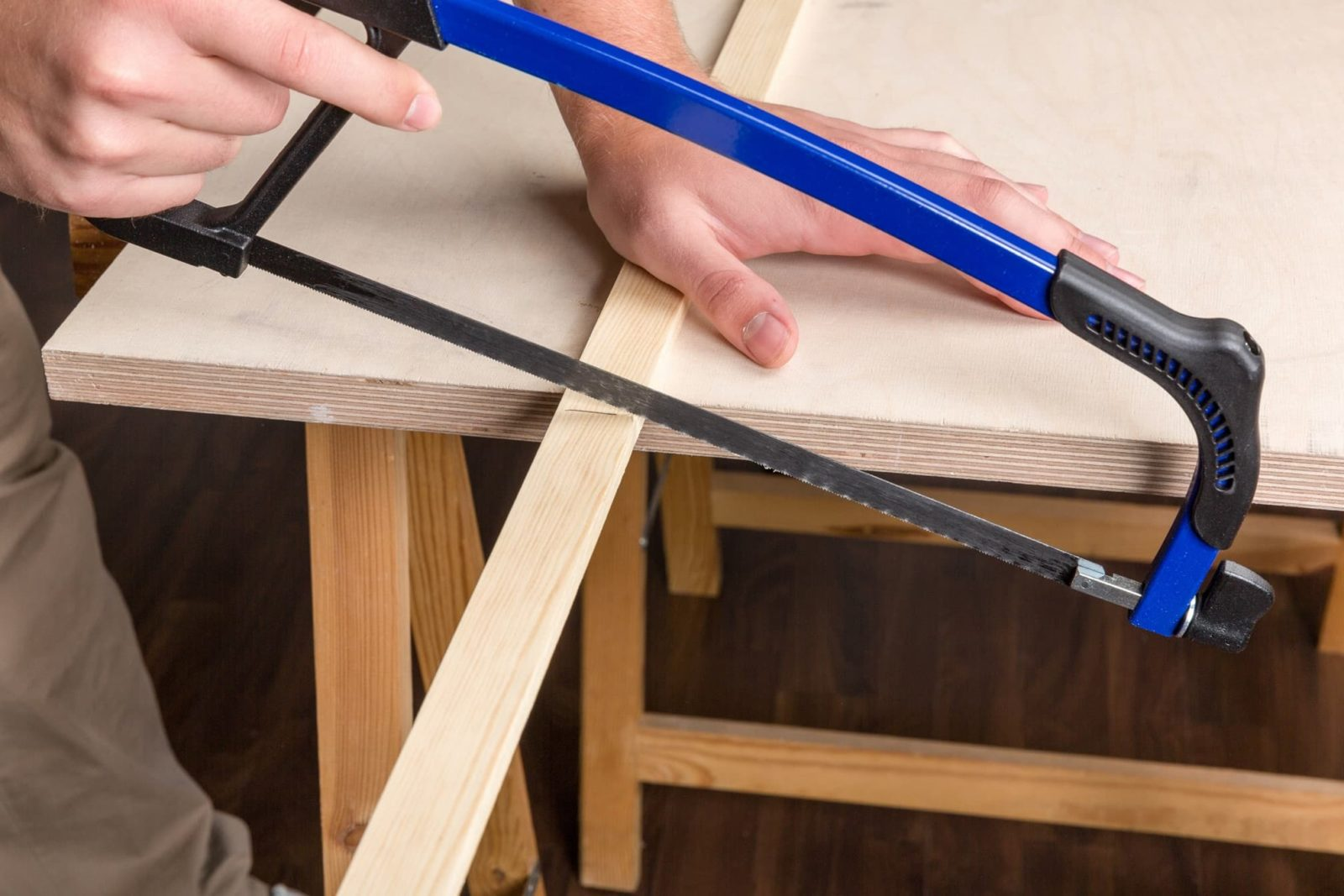 man using bow saw to cut through timber