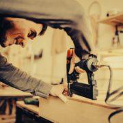 man using nail gun on workbench
