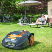 robotic lawn mower in action while woman lays on sunbed in garden