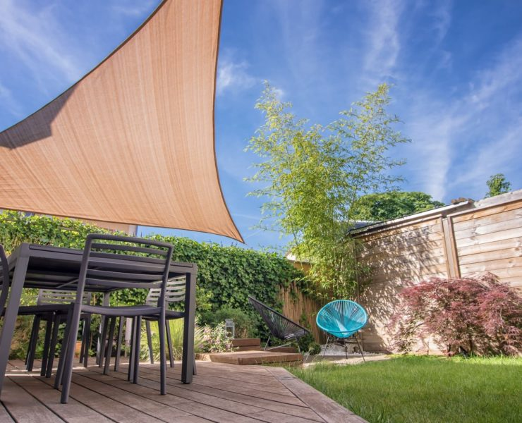 garden shade sail sat over decking and garden furniture