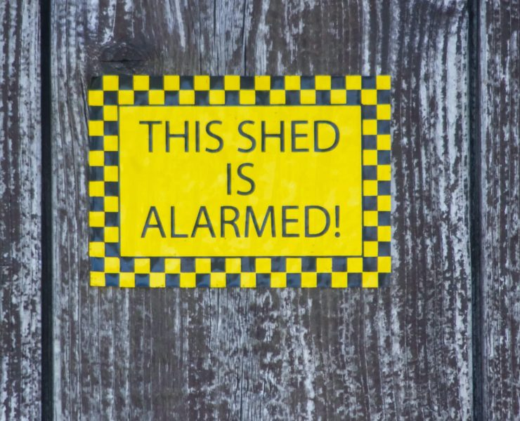 yellow sign that reads 'this shed is alarmed'
