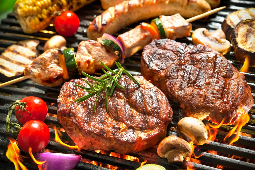 steak, skewers, sausages and veg on a hot grill
