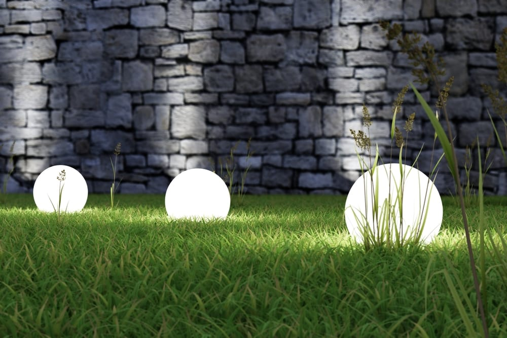 glowing light orbs on grass with dark grey wall background