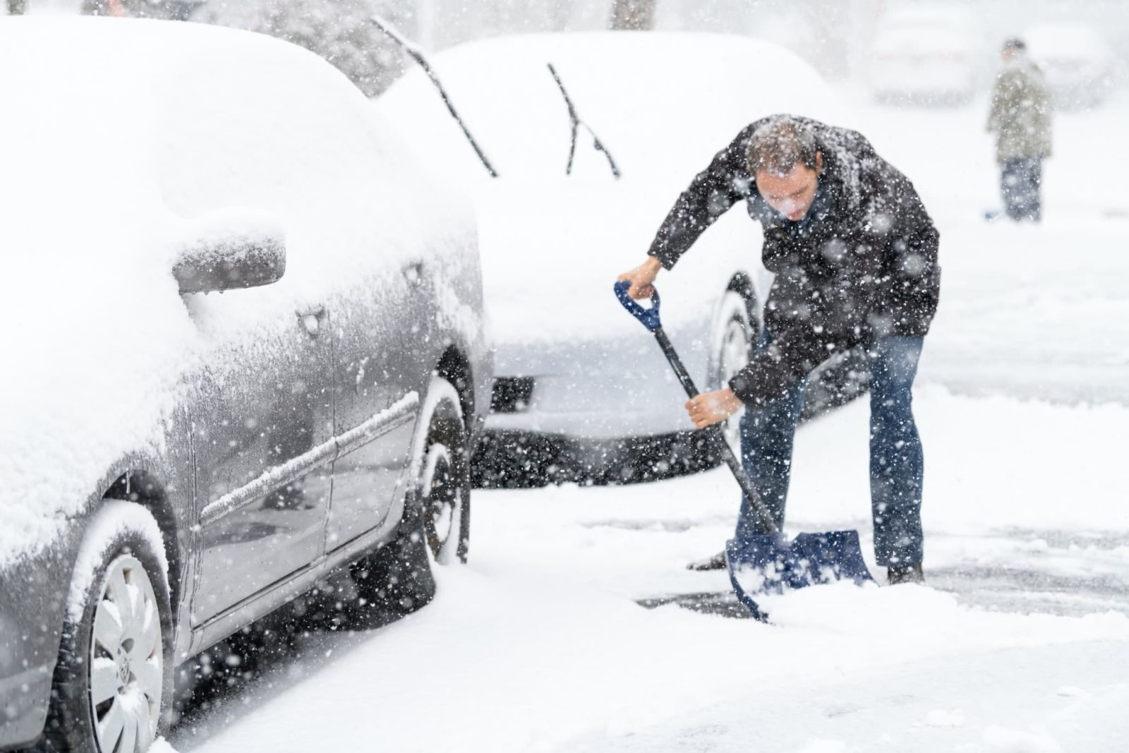 man shovelling snow in front of two cars