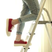 woman stood at height on step ladders