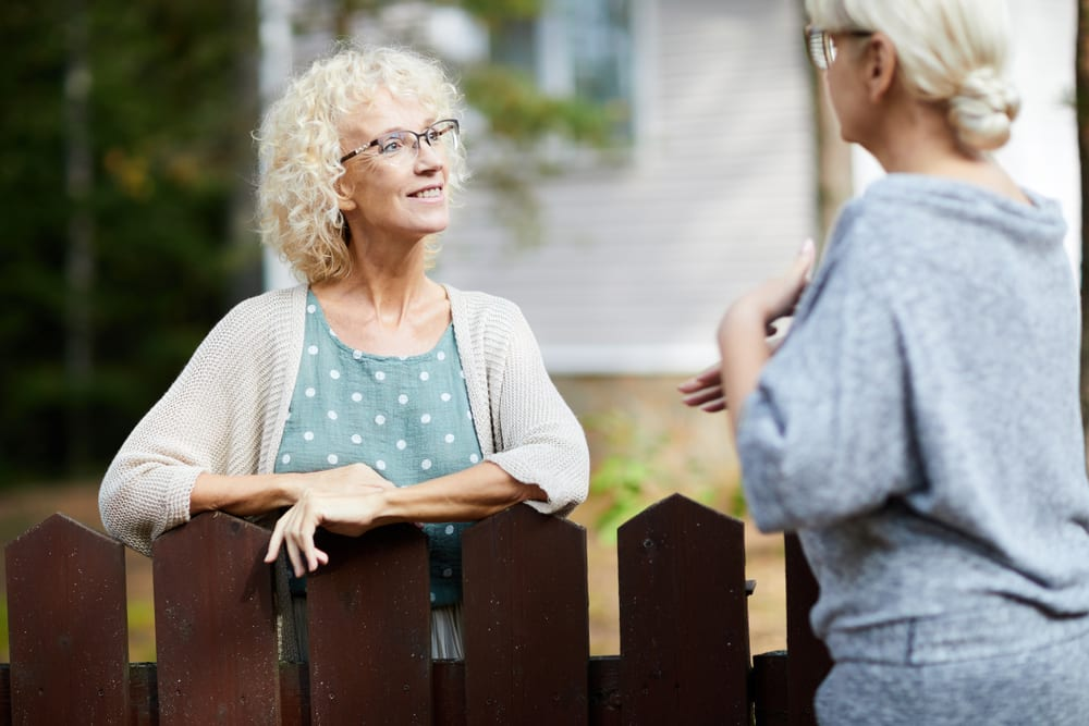 two older ladies chatting over fence