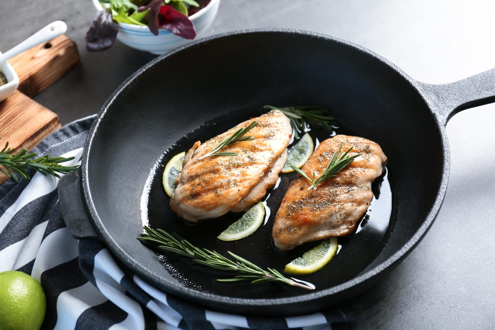 chicken breasts in a frying pan topped with rosemary and lemon