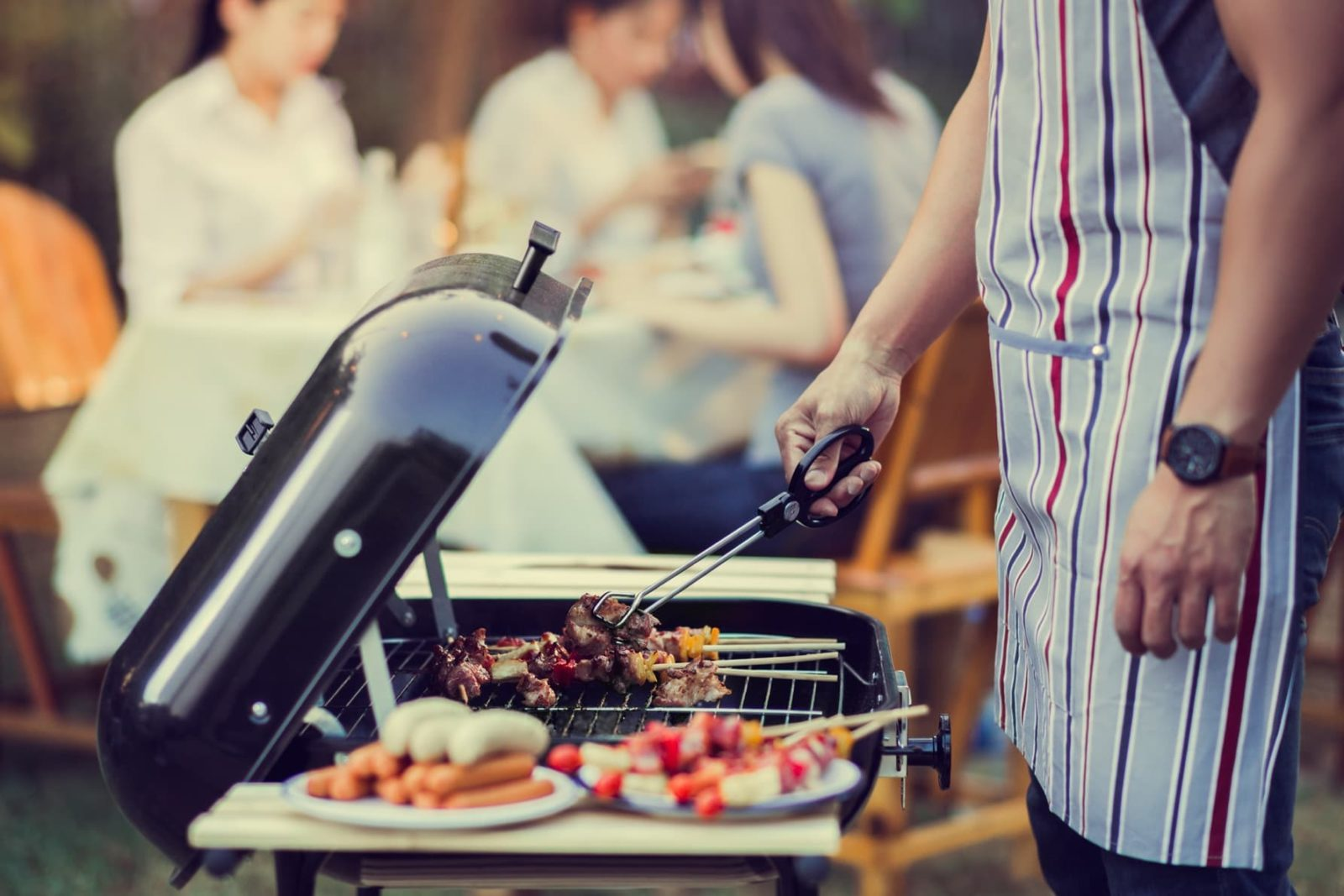 a bbq and side table with people eating in the background