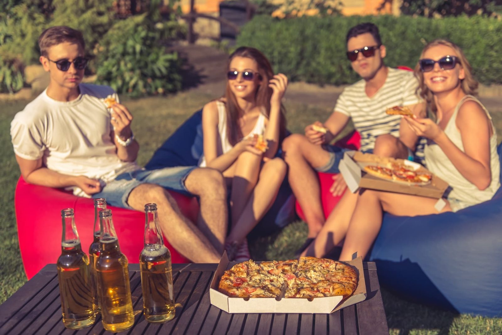 four youngsters sat on bean bags in garden