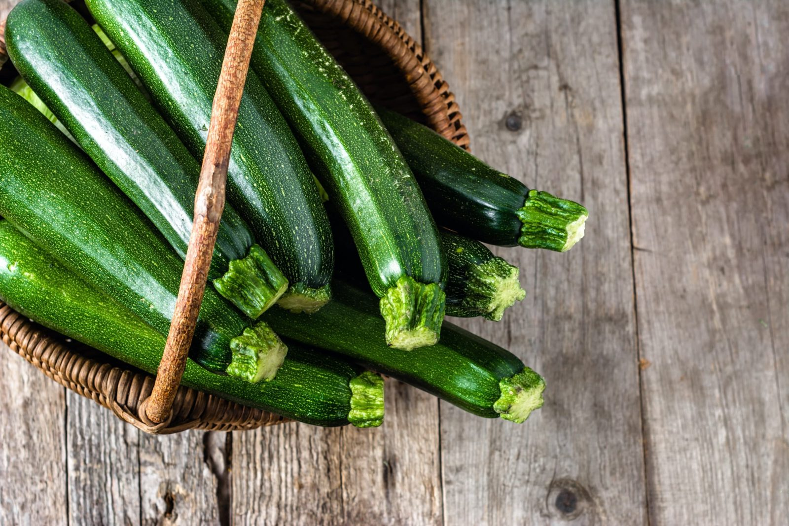 courgettes in a basket on a timber surface